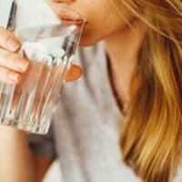 コップに入った水を飲む人