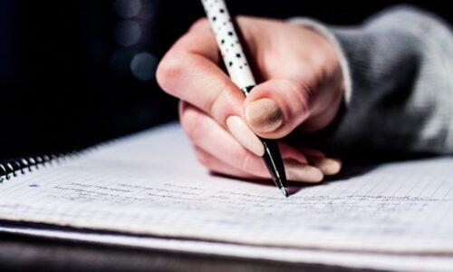 ノートに筆記している手